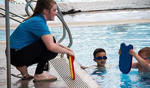 Swimming coach teaching kids